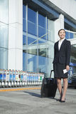 Traveler walking out of airport with rolling suitcase Stock Photo