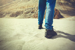 Traveler walking in the sand dune towards the hill - travel, vacation,recreation and adventure Stock Images