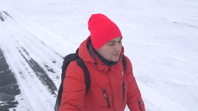 Traveler walks along the snow-covered ice of the lake. A traveler walks along the snow-covered ice of the lake holding an action camera in the hands of a self stock footage
