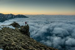 Traveler With Hiking Sticks Standing At The Edge Of The Cliff Above Clouds During Sunrise Royalty Free Stock Photo
