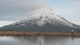 Traveler wlking to the view looking to the taranaki volcano in the north island of new zealand and with the reflection stock video footage