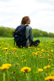 Traveler woman with a backpack. Sitting among green field with yellow dandelions. Tourist is out of focus Stock Photo