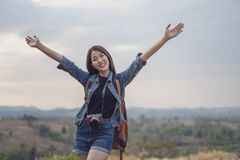 Traveler woman with backpack with arms raised stock photography
