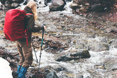 Traveler Woman with backpack hiking Travel Lifestyle. Concept active vacations outdoor river on background rainy moody weather Royalty Free Stock Photo