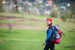Traveler woman with a backpack on the hill. Traveler woman in a red scarf on her head and blue jacket with a backpack looking at the camera, blurred greenery Stock Photos