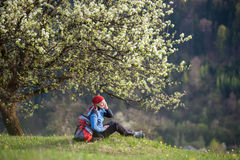 Traveler woman with a backpack near blooming tree. Old happy female with a backpack sit under blooming tree on top of hill with yellow wildflowers, green grass Royalty Free Stock Photo