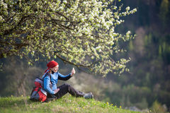 Traveler woman with a backpack near blooming tree. Smiling female with a backpack sit under blooming tree on top of hill with yellow wildflowers, green grass and Royalty Free Stock Images