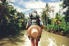Traveler woman with backpack standing near big tropical river at sunny day. Traveler woman with backpack standing near tropical river at sunny day Royalty Free Stock Image