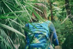Traveler woman with backpack walking on path in the tropical forest. At summer day Stock Photography