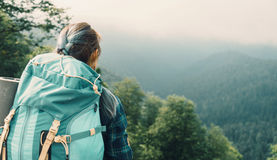 Traveler woman with backpack. Traveler young woman with backpack looking at the mountains in summer, rear view Stock Photo
