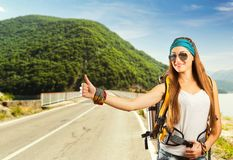 Traveler woman is catching a car. Happy traveler woman with backpack is catching a car on the road Stock Photo