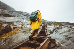 Traveler woman climbing up stairs in scandinavian mountains Stock Images