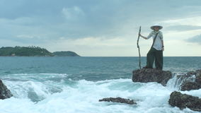 Traveler Woman On Coast With Cloudy Sky Background. Young woman in Asian clothing with wooden stick in beautiful sea nature landscape stock video