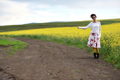 Traveler woman in dress hitchhiking in the countryside. Traveler young woman in dress hitchhiking in the countryside Royalty Free Stock Photos
