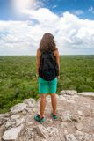 Traveler woman enjoys the view from the top of the Nohoch Mul pyramid in Coba Royalty Free Stock Image