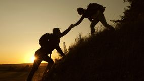 Traveler woman extends a hand to a man to a traveler climbing to the top of a hill. Tourists climb the mountain at. Traveler woman extends a hand to man to a stock video footage