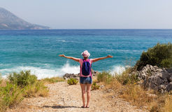 Traveler woman in front of sea. Traveler woman with a backpack and spaced apart arms standing in front of the sea Royalty Free Stock Photography