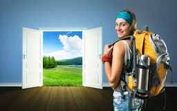 Traveler woman is going to nature doors. Traveler woman with backpack is going to opened doors to the meadow Stock Image