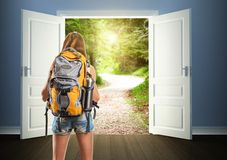 Traveler woman is going to opened doors. Traveler woman with backpack is going to opened doors to the forest Royalty Free Stock Images