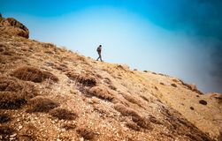 Traveler woman hiking. Woman hiking along beautiful mountains, active female with backpack traveling along high mountaing, enjoying vacation and freedom royalty free stock photography