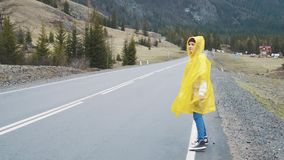 Traveler woman hitchhiking on a Cloudy road and walking. Young happy backpacker woman looking for a ride to start a stock video footage