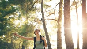Traveler woman hitchhiking on a sunny forest road. Tourist girl looking for ride to start her journey royalty free stock images
