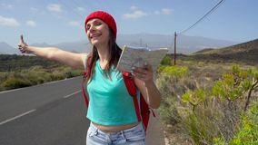 Traveler woman hitchhiking on a sunny road and walking. Backpacker woman looking for a ride to start a journey on a