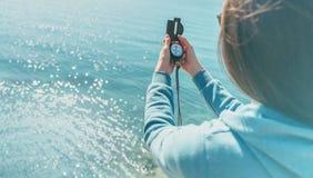 Traveler woman holding a compass on coast Stock Photos