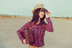 Traveler woman looks through binoculars Stock Images