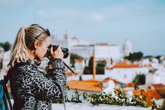 Traveler woman make a picture of Lisbon cityscape. The National Pantheon and the towels of Vicente de Fora come into stock photography