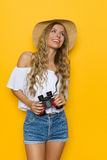 Traveler Woman Observe. Smiling beautiful blond young woman in jeans shorts, white shirt and straw hat, holding binoculars and looking away. Three quarter length Royalty Free Stock Image