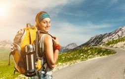 Traveler woman outdoor. Happy traveler woman with backpack near the mountain road Stock Photos