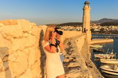 Traveler woman photographer with professional camera takes shot of Rethymno,Crete, Greece. stock photography