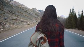 Traveler woman picking up her backpack. Backpacker woman lifts her bag from the road in the morning countryside. Background stock footage