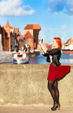 Traveler woman red hair girl with camera old town Gdansk Stock Photo