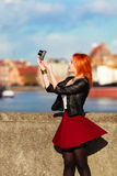 Traveler woman red hair girl with camera old town Gdansk Royalty Free Stock Photography
