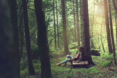 Traveler woman rests in a mysterious and surreal forest royalty free stock photo