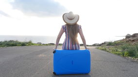 Traveler woman sits on suitcase and looks away on road. Travel concept stock video footage