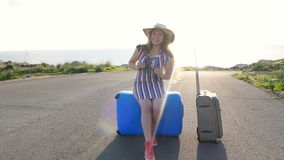 Traveler woman sits on suitcase and looks away on road. Travel concept stock footage