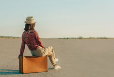 Traveler woman sitting on suitcase on road, copy-space Royalty Free Stock Photos