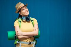Traveler woman standing against blue wall with backpack. Smiling girl wearing hat Royalty Free Stock Photography