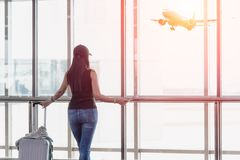 Traveler woman standing and hand holding luggage bag see the airplane at the airport glass window. Royalty Free Stock Photo