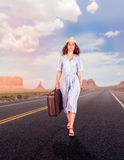 Traveler woman with suitcase, walking on the road. Blue sky with clouds and rocky mountains on the background. Travel concept Stock Image