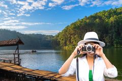 Traveler woman take a photo and siting on the terrace at resort on enjoy and relax with the outside nature. royalty free stock image