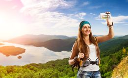 Traveler woman is taking selfie outdoor. Pretty traveler woman with backpack is taking selfie on the top of mountain Stock Photos
