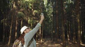 Traveler woman in a hat trying to catch a cell signal on the phone in the forest, no signal on the phone