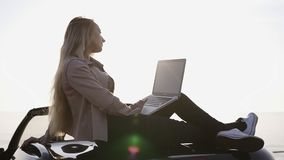 Traveler woman using laptop on car road trip. Young woman reading and typing on computer, using mobile internet. Relaxing sitting on her cabriolet car with stock footage