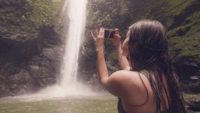 Traveler woman using smartphone for photo splashing waterfall in jungle forest. Woman tourist shooting video tropical stock footage