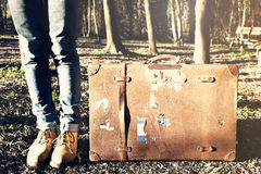 Traveler woman waits with her suitcase to leave in the woods Royalty Free Stock Photos