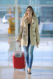 Traveler woman walking carrying a suitcase in an airport. Front view of a traveler woman walking carrying a suitcase in an airport corridor Stock Images